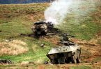 Two confiscated destroyed Serbian Army BOV-VP Wheeled Armored Personnel Carrier (APC) sit in a field. - wikimedia commons